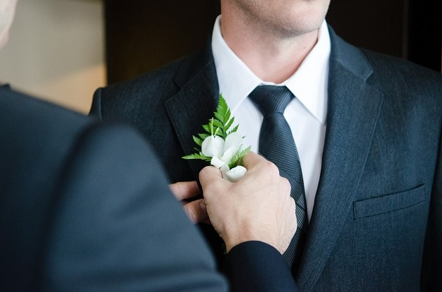Best man adjusting grooms button hole