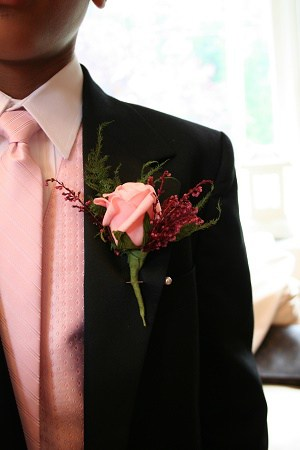 A groom wearing a pink shirt and tie