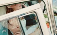 A bride in a car holding a bouquet